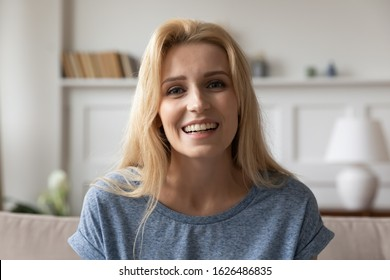 Head shot close up portrait of attractive smiling young blonde woman. Pleasant millennial girl looking at camera, holding video call with parents or recording vlog for personal channel at home.