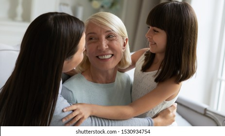 Head shot close up portrait happy 3 generations women family spending leisure time together. Overjoyed young lady cuddling embracing hugging smiling middle aged mother and happy little daughter.