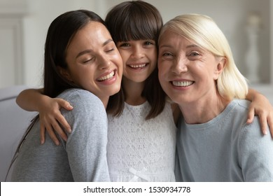 Head shot close up portrait happy adorable little preschool girl embracing cuddling hugging young smiling mother and mature granny. Laughing 3 generations women family sitting together on sofa.