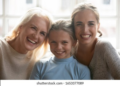 Head shot close up portrait happy excited smiling 3 generations women, middle aged grandmother, young mommy and adorable school granddaughter laughing, looking at camera, bonding, having fun together.