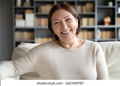 Head shot close up portrait happy healthy middle aged woman sitting on comfortable couch at home. Smiling pleasant 50s elderly mother looking at camera, posing for photo in modern living room.