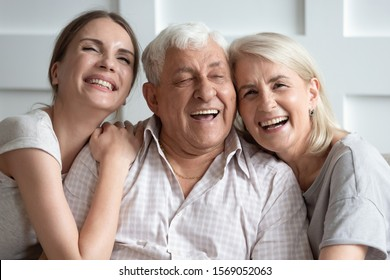 Head shot close up portrait overjoyed attractive young woman having fun with happy older parents. Laughing two generations enjoying free leisure family time together at home, posing for photo.