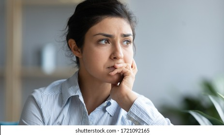 Head shot close up sad young indian woman thinking of problems, looking away. Unhappy millennial hindu girl student suffering from personal professional troubles, feeling depressed at home.