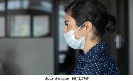 Head shot close up side view concentrated indian ethnic female worker employee wears medical facial mask, working in corporate office. Cautious young businesswoman preventing spreading corona virus.
