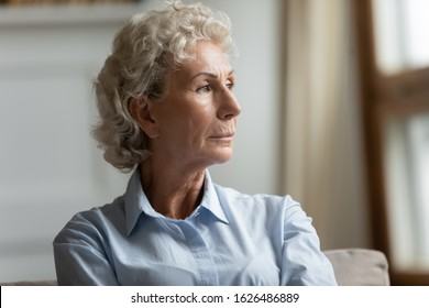 Head shot close up thoughtful middle aged grandmother looking away. Pensive older mature grandmother thinking of health or personal problems, feeling lonely in living room, negative thoughts concept.