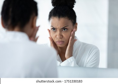 Head shot close up unhappy African American young woman checking skin, touching cheeks, angry girl wearing white bathrobe worried about mimic wrinkle or acne, looking in mirror, standing in bathroom