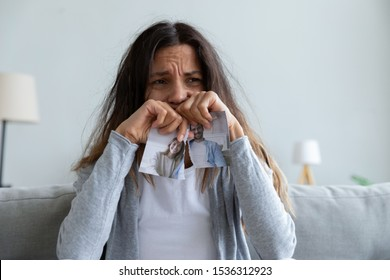 Head shot depressed unhappy millennial mixed race girl sitting at home alone, regretting relationship break up, crying, thinking of betrayal, relations problems, holding torn photo of smiling couple.