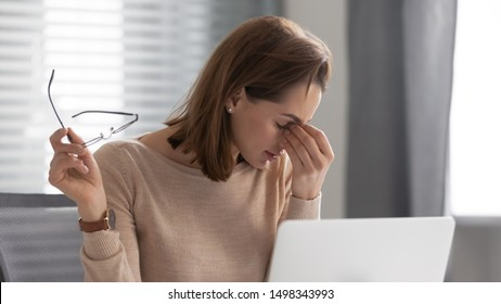 Head shot exhausted female employee took off glasses, massaging nose bridge, suffering from dry eyes syndrome. Tired executive manager feeling pain in eyes, overloaded with computer work at office.