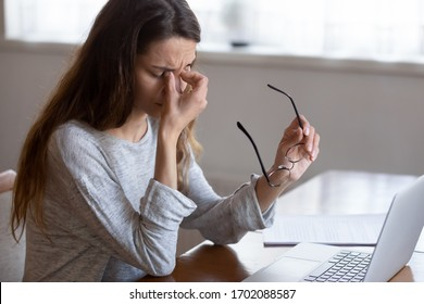 Head shot exhausted young woman taking off glasses, suffer from eyes strain due to computer overwork. Tired unhealthy millennial mixed race lady having painful feelings, blurred vision syndrome.