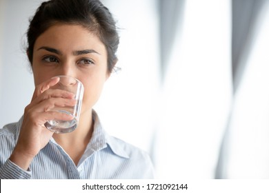 Head shot face close up healthy young indian girl drinking pure water. Pretty millennial mixed race hindu woman quenching thirst, enjoying daily healthcare habit, keeping nutrition weight loss diet.