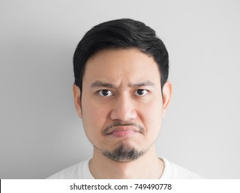 Head shot of grumpy face Asian man.