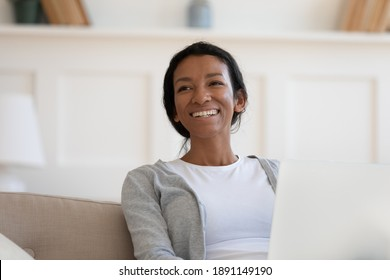 Head shot happy dreamy young african ethnicity woman sitting on couch with laptop, looking in distance. Smiling millennial mixed race freelance worker distracted from doing online job at home.