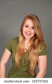 head shot of happy teen girl with blonde hair looking at camera