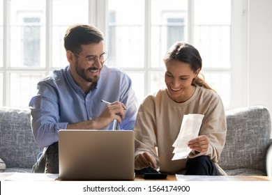 Head shot happy young family couple planning monthly budget, sitting together on cozy sofa, using computer software. Smiling mixed race wife calculating income and outcome together with husband.