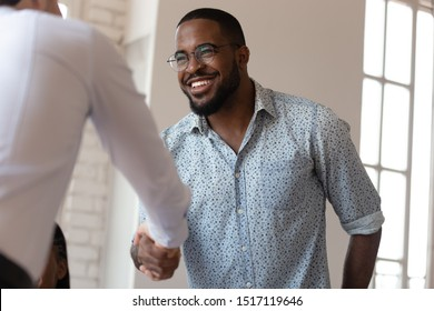 Head shot image joyful african american millennial worker shaking hands with colleague. Confident business partners making agreement before contract signing. Happy teammate thanking for help with job.