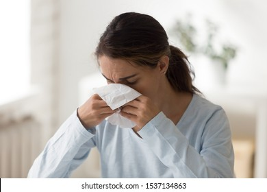 Head shot image young unhealthy mixed race woman using paper tissue, suffering from seasonal allergy or caught cold. Unhappy millennial lady feeling unwell, wiping runny nose. Health care concept.