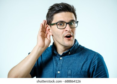 Head shot of man, hand to ear gesture trying secretly listen gossip or conversation or news. Shocked by what he hears. Isolated on grey background