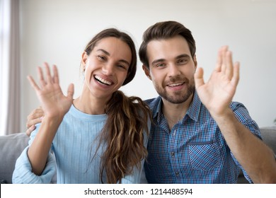 Head shot married couple sitting on sofa at home. Portrait wife and husband waving hands looking at camera smiling saying hello greeting or goodbye. First acquaintance or online communication concept
