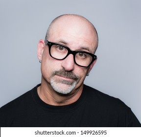 Head shot of a middle aged bald man with a goatee, black glasses and a black shirt looking at the camera with his head tilted to the side