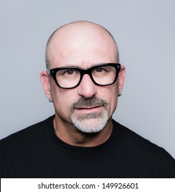Head shot of a middle aged bald man with a goatee, black glasses and a black shirt looking in the to camera with an angry look