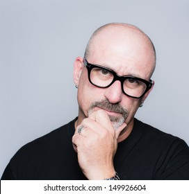Head shot of a middle aged bald man with a goatee, black glasses and a black shirt looking at the camera in deep thought with his hand to his face