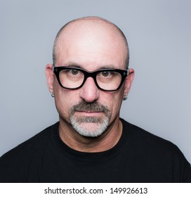 Head shot of a middle aged bald man with facial hair, black rim glasses and a black T-shirt looking at the camera very concerned with a gray background