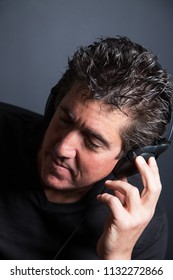 head shot of a middle aged man enjoying music on his headphones with his eyes closed