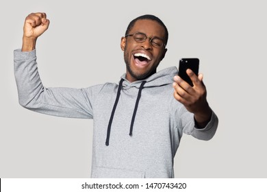 Head shot overjoyed happy millennial african american man holding smartphone, looking at screen, reading lottery winner notification, celebrating achievement, isolated on grey studio background.