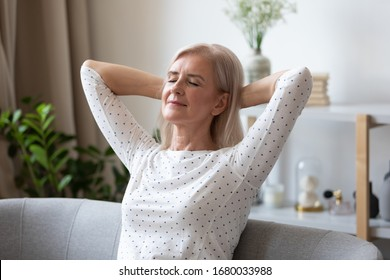 Head shot peaceful middle aged pleasant woman crossed hands behind head, daydreaming on comfortable sofa in modern living room. Attractive mature lady relaxing meditating with closed eyes at home.