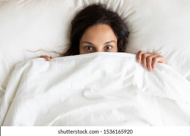 Head shot portrait above top view funny mixed race millennial girl lying on soft white pillows, hiding behind duvet in bedroom. Positive young biracial woman having fun after waking up in morning.