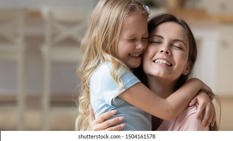 Head shot portrait adorable blonde adopted little girl cuddling young smiling mommy, feeling happiness. Joyful family of two hugging embracing bonding together at home, enjoying sweet tender moment.