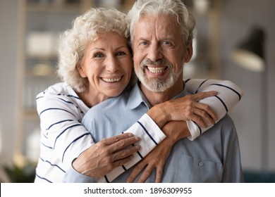 Head shot portrait of affectionate loving middle aged hoary beautiful woman cuddling from back smiling old husband. Happy loving mature married family couple looking at camera, posing for photo.