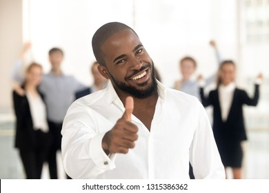 Head shot portrait african businessman show thumbs up feels satisfied received high-quality service overjoyed employees pose on background. Successful business people, recommendation, feedback concept