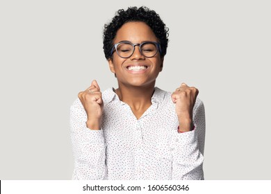 Head shot portrait african woman clenched fists closed eyes waiting a miracle, having desire win money in lottery begging for fortune, moment dream will come true concept, isolated on gray background