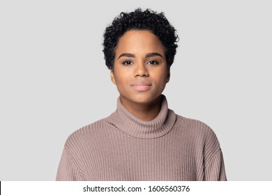 Head shot portrait African young woman having short black hairs wears knitted sweater posing isolated on gray background, serious beautiful 20s mixed-race girl look at camera, natural beauty concept