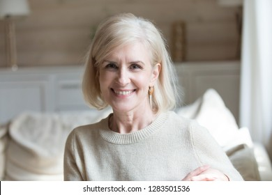 Head shot portrait aged blond woman in casual wear sitting in living room in comfortable modern home smiling posing for camera. Grey haired senior female spending time alone feeling good and healthy