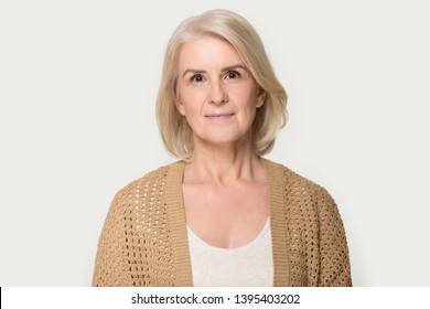 Head shot portrait attractive mature fifty year woman wearing brown knitted cardigan pose on grey studio background, healthy retired female natural beauty, health care, medical insurance concept image