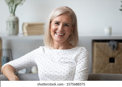 Head shot portrait attractive middle-aged woman with charming healthy candid smile sitting on couch posing looking at camera feels happy enjoy photo shooting has positive mood carefree life concept