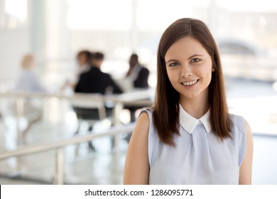 Head shot portrait of attractive young but experienced and skilled business coach standing apart of employees smiling looking at camera. Intern started career at large company feel satisfied and happy
