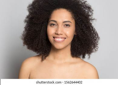 Head shot portrait beautiful African American girl with bare shoulders looking at camera, happy young female with perfect smooth skin isolated on grey background, skincare and natural beauty concept