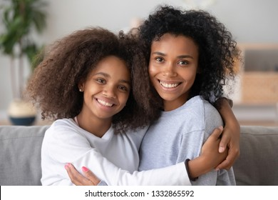 Head shot portrait of biracial daughter and young mommy sitting on couch at home and embracing celebrating mothers day. New mom for adopted teen kid, relative people elder and younger sisters concept