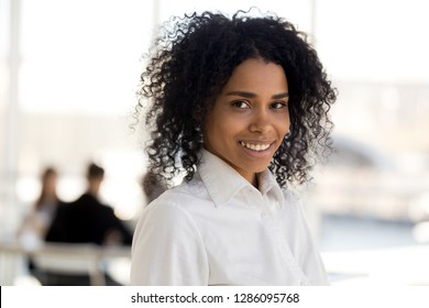 Head shot portrait of biracial mixed race attractive smiling successful business lady posing looking at camera. Millennial business woman starting career in international company feels happy and proud