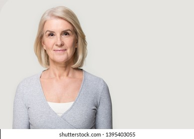 Head shot portrait blond aged woman pose aside on grey wall copy space for ad text, mature healthy female advertise facial skin treatment cosmetics cosmetology and aesthetic medicine procedure concept