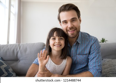 Head shot portrait of cheerful diverse family young man sitting on sofa at home with daughter have video call using computer, wave hands greeting or say goodbye to friend and smiling looking at camera