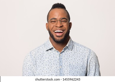 Head shot portrait of cheerful laughing young African American man in glasses isolated on studio background copy space, funny guy with wide beaming healthy smile looking at camera, feeling happy