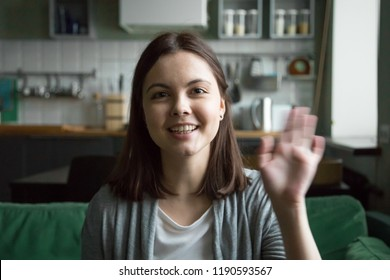 Head shot portrait of cheerful young woman sitting on sofa at home. Girl in casual clothes have video call using computer, wave her hand greeting or say goodbye to friend and smiling looking at camera