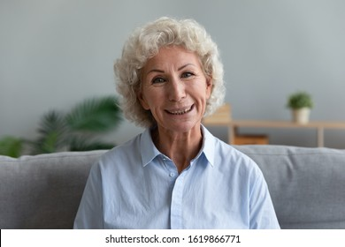 Head shot portrait close up beautiful older woman with toothy smile looking at camera, sitting on couch in living room at home, mature female making video call, teacher holding online lesson