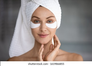 Head shot portrait close up beautiful woman with hydrogel patches under eyes looking at camera, pretty young female wearing white towel on head doing face care procedure in bathroom, healthy skin