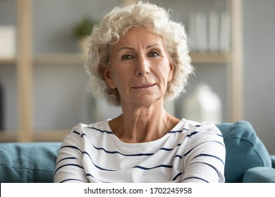 Head shot portrait close up beautiful aged mature woman with grey curly hair sitting on cozy couch, posing for photo at home, attractive older senior female looking at camera, natural old beauty