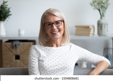 Head shot portrait close up positive satisfied mature woman in glasses sitting on sofa at home, happy older female with toothy smile looking at camera, posing for photo on comfortable couch